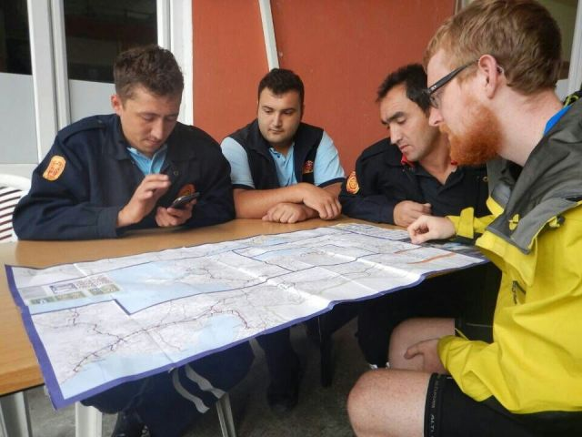 A team of helpers pouring over their map of Turkey for our route